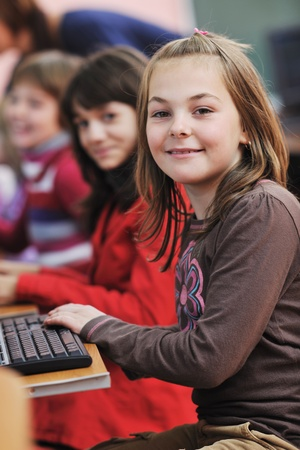 it education with children group  in school at computer science class learning leassons and practice typing  photo