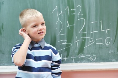 happy young boy at first grade math classes solving problems and finding solutions photo