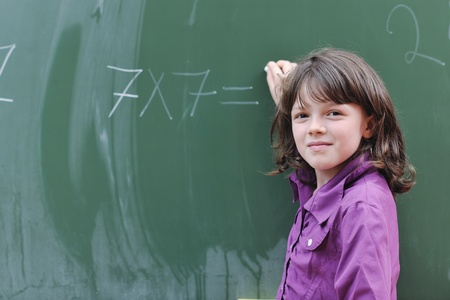 happy school girl on math classes finding solution and solving problems photo