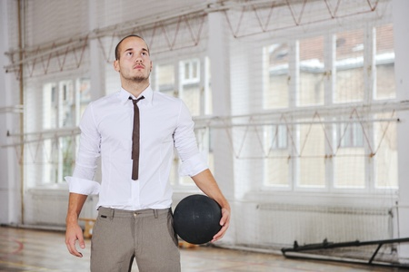 modern businessman: young business man basket player hold basketball ball and representing success and retirement in sport like also sports management concept