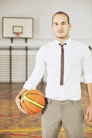 coach sport: young business man basket player hold basketball ball and representing success and retirement in sport like also sports management concept