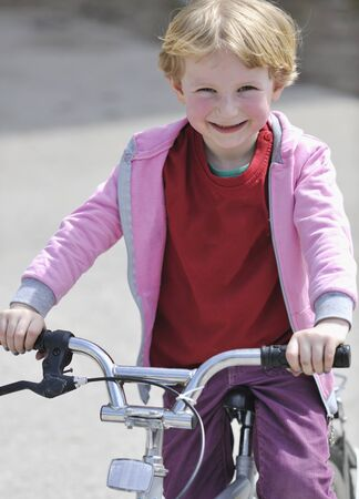 cute little girl learn to drive bicyle at sunny day  photo