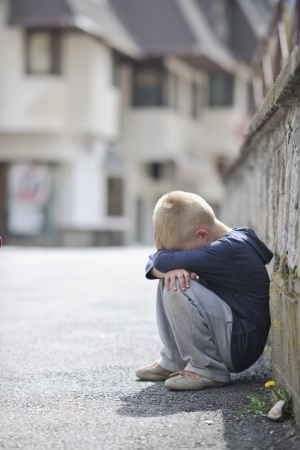 sad and unhappy alone child cry and have emotion problem on street photo