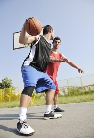 basketball game: streetball basketball game with two young player at early morning on city court