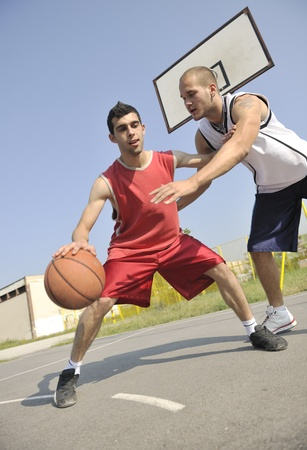dribble: streetball basketball game with two young player at early morning on city court