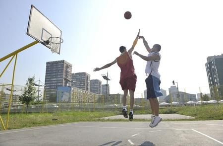 cancha de basquetbol: Partido de baloncesto de Streetball con dos jugadores j�venes en temprano en la ma�ana en la cancha de la ciudad