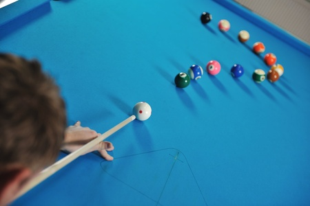 young pro billiard player finding best solution and right angle at billard or snooker pool sport  game  photo
