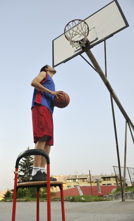 outdoor basketball court: basketball player practicing and posing for basketball and sports athlete concept