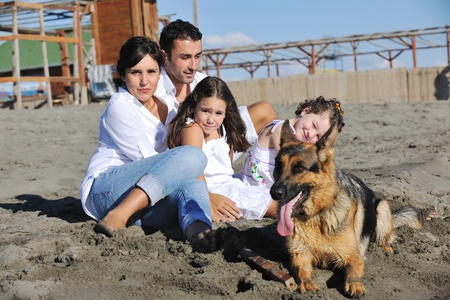happy young family in white clothing have fun and play with beautiful dog at vacations on beautiful beach  photo