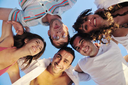 happy young friends group team huging have fun and celebrate  on the beach at the sunset photo