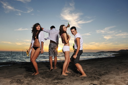 beach party: happy young friends group have fun and celebrate while jumping and running on the beach at the sunset Stock Photo