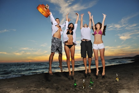 happy young friends group have fun and celebrate while jumping and running on the beach at the sunset photo