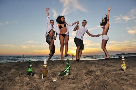 fiestas discoteca: Grupo de amigos de j�venes felices divertirse y celebrar mientras saltando y que se ejecutan en la playa en la puesta de sol
