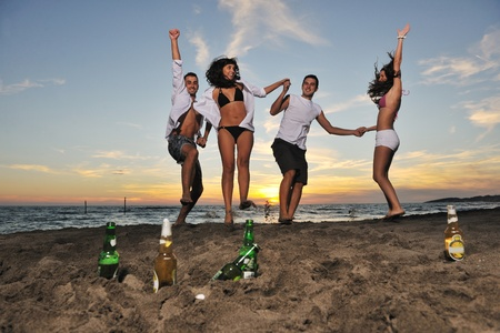 happy young friends group have fun and celebrate while jumping and running on the beach at the sunset Stock Photo - 8327747