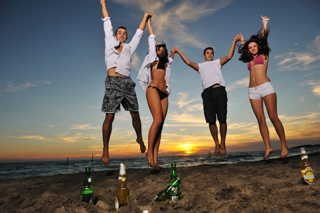 happy young friends group have fun and celebrate while jumping and running on the beach at the sunset Stock Photo