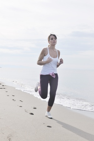 young healthy woman jogging and running at beach at early morning  photo