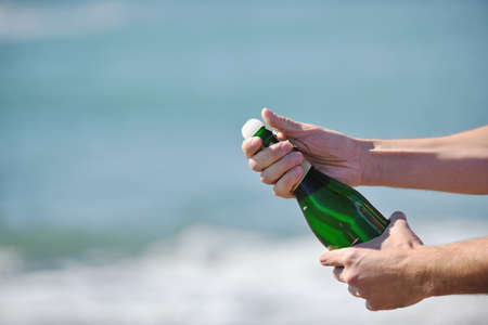 man hands open bottle of champagne alcohol and wine drink outdoor on party celebration event  photo