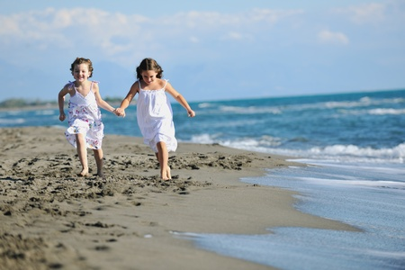 happy two little girls have fun and joy time at beautiful beach while running from joy  Stock Photo - 8326377