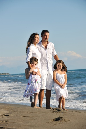 activity holiday: happy young family in white clothing have fun at vacations on beautiful beach