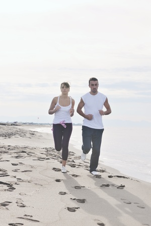 happy young couple running and jogging on beach at early morning photo