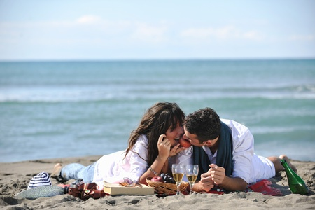 happy young couple enjoying  picnic on the beach and have good time on summer vacations photo