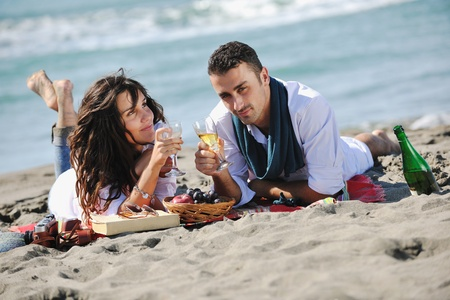happy young couple enjoying  picnic on the beach and have good time on summer vacations Stock Photo - 8327960