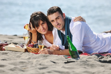 happy young couple enjoying  picnic on the beach and have good time on summer vacations Stock Photo - 8327944