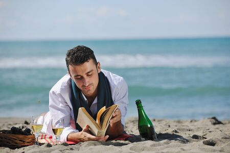 young man relaxing on beach at beautiful sunny day while reading book representing summer school and education concept photo