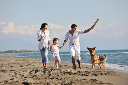 happy young family in white clothing have fun and play with beautiful dog at vacations on beautiful beach Stock Photo - 8328053