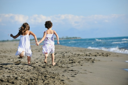 kids playing beach: happy two little girls have fun and joy time at beautiful beach while running from joy  Stock Photo
