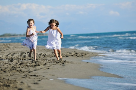 happy two little girls have fun and joy time at beautiful beach while running from joy  photo