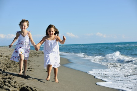 having fun: happy two little girls have fun and joy time at beautiful beach while running from joy  Stock Photo