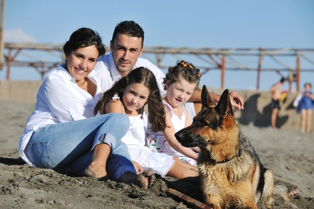 dog summer: happy young family in white clothing have fun and play with beautiful dog at vacations on beautiful beach  Stock Photo