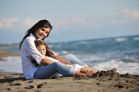 family portrait of young beautiful mom and daughter on beach photo
