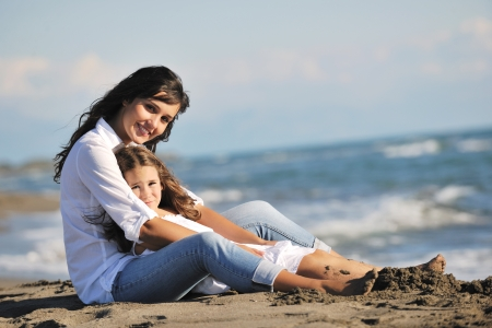 mom daughter: family portrait of young beautiful mom and daughter on beach Stock Photo