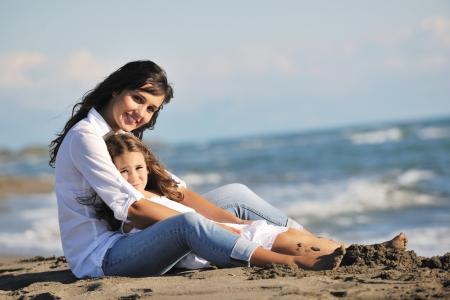 mama e hija: Retrato de familia de la joven madre hermosa y su hija en playa