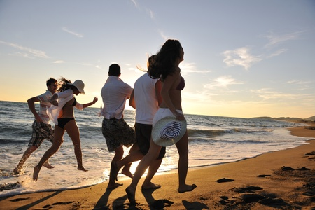 happy young people group have fun white running and jumping on beacz at sunset time photo