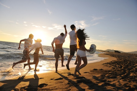 friendship women: happy young people group have fun white running and jumping on beacz at sunset time Stock Photo