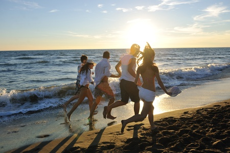 happy young people group have fun white running and jumping on beacz at sunset time Stock Photo - 8328174