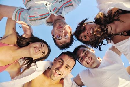 feliz huging de equipo de grupo de jóvenes amigos, divertirse y celebrar en la playa en la puesta de sol