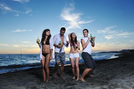 fiesta amigos: Grupo de amigos de j�venes felices divertirse y celebrar mientras saltando y que se ejecutan en la playa en la puesta de sol