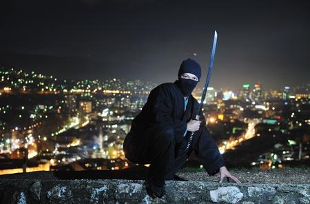 japanese ninja: ninja assasin hold katana samurai old martial weapon swordat night with city lights in background
