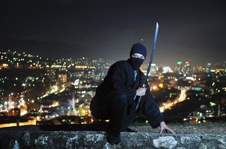 katana: Ninja assasin houden katana samurai oude martial wapen swordat nacht met stadslichten in achtergrond