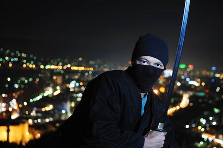 ninja assasin hold katana samurai old martial weapon swordat night with city lights in background Stock Photo - 8328031