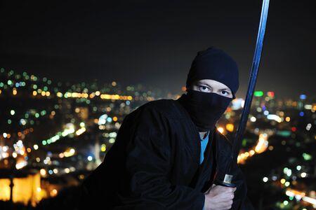 ninja assasin hold katana samurai old martial weapon swordat night with city lights in background photo