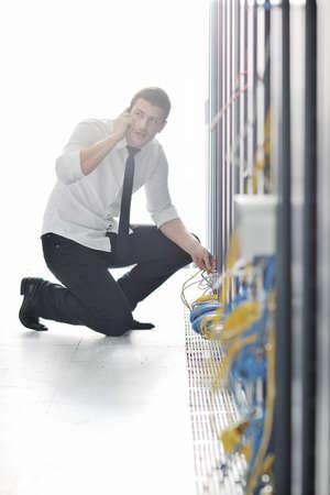 negocio joven hombre equipo ciencia engeneer hablando por tel�fono celular en la sala de servidores de centro de datos de red pidiendo ayuda y soluciones r�pidas y servicios Foto de archivo - 8437090