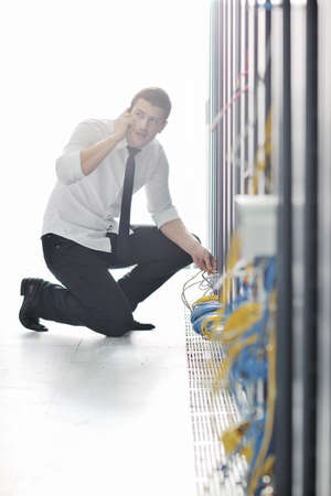 young business man computer science engeneer talking by cellphone at network datacenter server room asking  for help and fast solutions and services Stock Photo - 8437090
