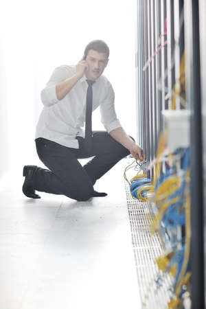 young business man computer science engeneer talking by cellphone at network datacenter server room asking  for help and fast solutions and services Stock Photo - 8437085