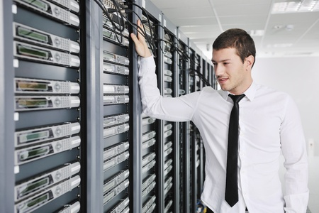 internet service provider: young handsome business man  engeneer in datacenter server room