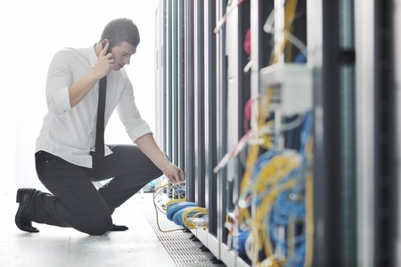 web solution: young business man computer science engeneer talking by cellphone at network datacenter server room asking  for help and fast solutions and services Stock Photo